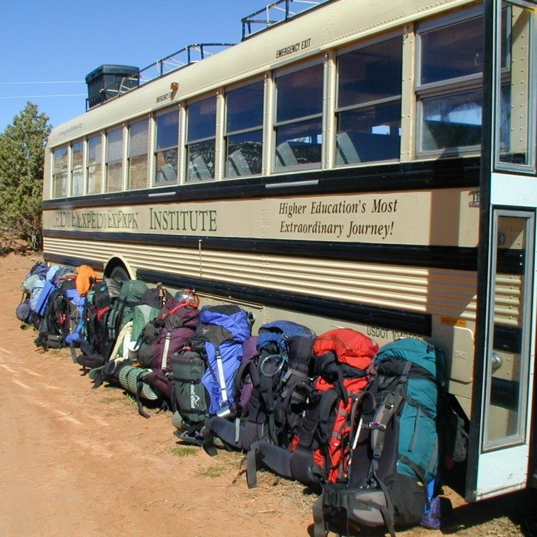 Group of packs leaning on bus after Rainbow Bridge backpack